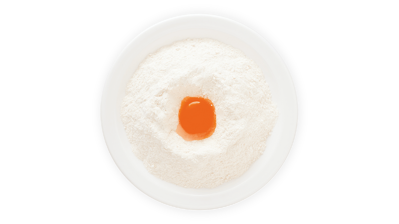 egg yolk in a bowl of flour